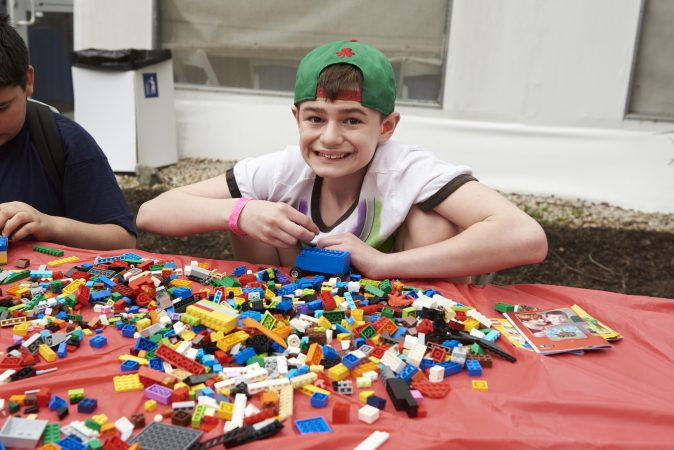 Brayden Tiscio, 12, builds a lego truck at the Lego table at the 20th Annual Autism Awareness Day event at the Philadelphia Zoo.  Brayden was diagnosed with Autism when he was three. (Natalie Piserchio for WHYY)