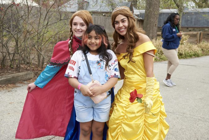 Yancy Estrada, 9, poses with Caroline Nowak as Snow White and Nicole Gonzales as Bell, at the 20th annual Autism Awareness Day at the Philadelphia Zoo. (Natalie Piserchio for WHYY)