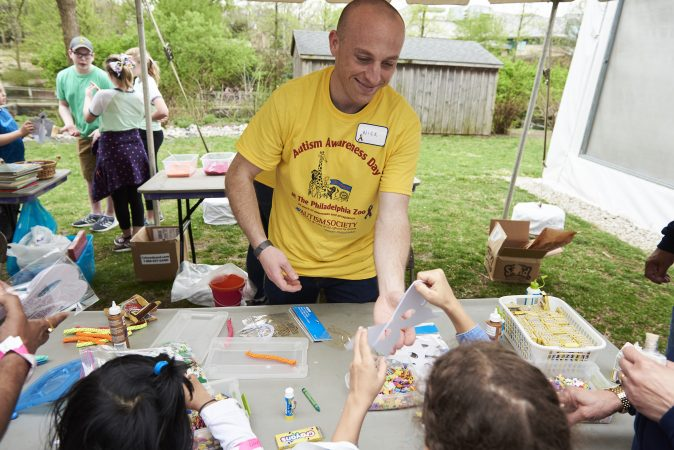 Nick Timer, a volunteer at Autism Awareness day at the Philadelphia Zoo, hands out art materials to children at an arts and crafts table at the event. (Natalie Piserchio for WHYY)