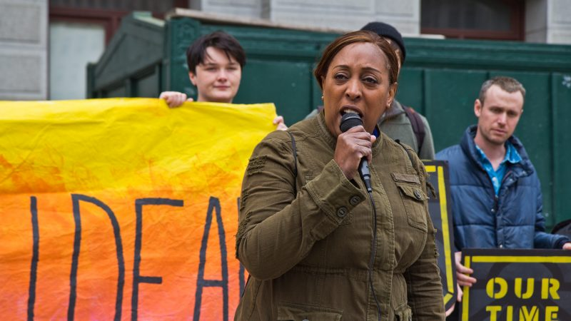 8th District city council candidate Tonya Bah speaks at New Sunrise Movement's New Green Deal Rally at City Hall Monday. (Kimberly Paynter/WHYY)