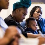 Thaashae Reingoud (center) takes notes as her son, Amir, sits on her lap at the