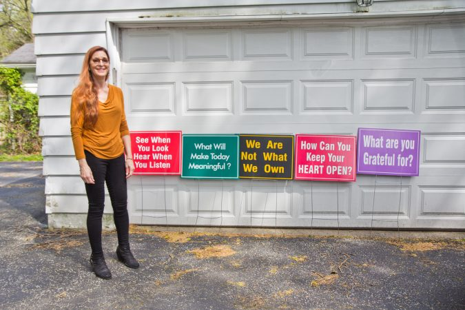 Meg Miller, a Lower Merion resident, with a few of her favorite signs that she displays on her property. (Kimberly Paynter/WHYY)
