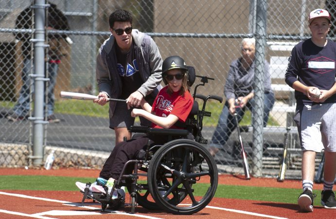 Devon Reed takes her turn at bat helped by Baily Otto, a volunteer from Stockton University, during opening day at the South Jersey Field of Dreams in Absecon N.J. (Anthony Smedile for WHYY)