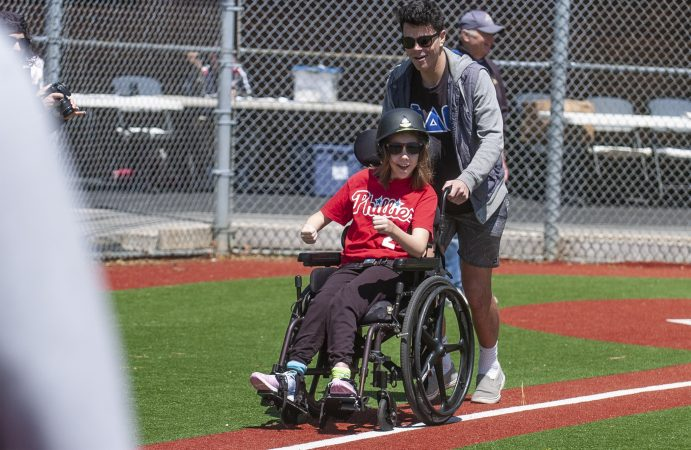 Devon Reed, 12, makes her way to first base with help from Baily Otto, a volunteer from Stockton University, during opening day at the South Jersey Field of Dreams. (Anthony Smedile for WHYY)