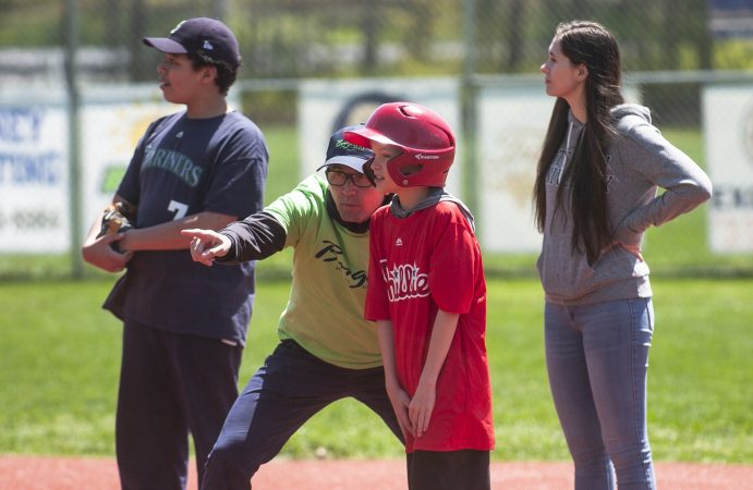James Bruno, a volunteer from The Borgata in Atlantic City helps Nick Miazga navigate the bases during opening day at the South Jersey Field of Dreams in Absecon. (Anthony Smedile for WHYY)