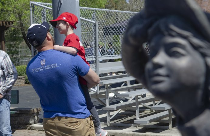 Mike Eykyn holds his son Drew during opening day at the South Jersey Field of Dreams in Absecon, New Jersey. (Anthony Smedile for WHYY)