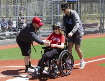 Rob Reed congratulates Devon Reed as she crosses home plate with help from Baily Otto, a volunteer from Stockton University, during opening day at The South Jersey Field of Dreams in Absecon, New Jersey. The Field of Dreams is a place where physically and mentally disabled children and adults can participate in the game of baseball. (Anthony Smedile for WHYY)