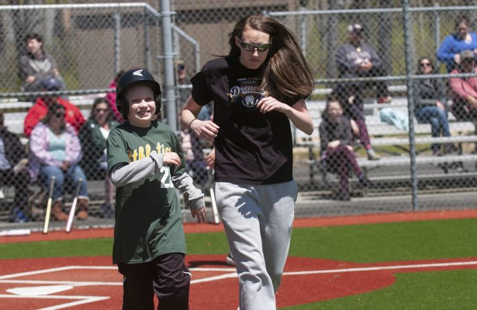 Toby Bates from Galloway Township runs to first base with Liz Champion during opening day at the South Jersey Field of Dreams. (Anthony Smedile for WHYY)