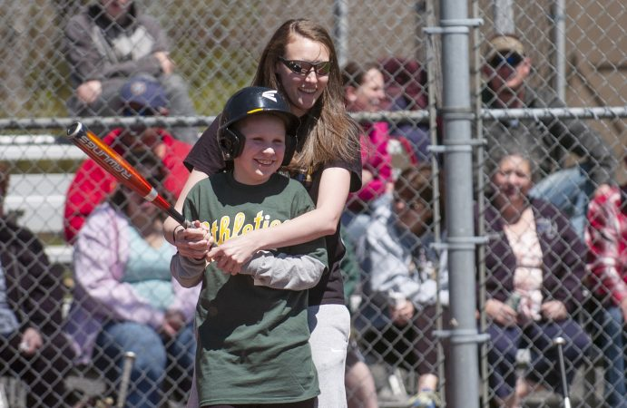 Toby Bates from Galloway Township gets up to bat with help from his friend Liz Champion during opening day at the South Jersey Field of Dreams. (Anthony Smedile for WHYY)