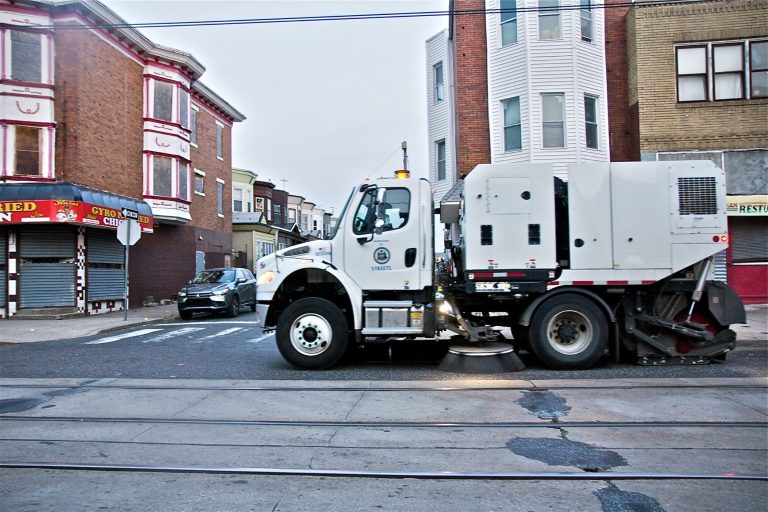 A city street sweeper cleans Chester Avenue in Southwest Philadelphia. (Kimberly Paynter/WHYY)