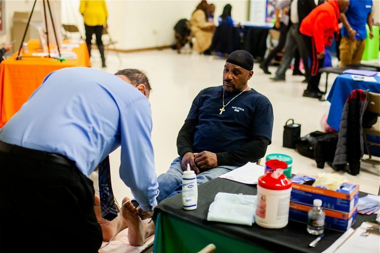Dr. Ronald Renzi performs an ultrasound on Russell Davis to check on blood circulation in screenings for peripheral vascular disease during a health and wellness clinic at Enon Tabernacle Baptist Church in Mount Airy. (Brad Larrison for WHYY)