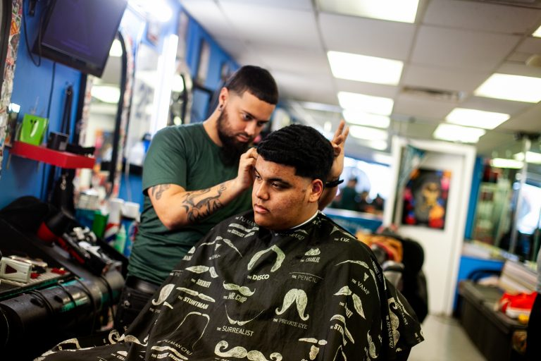 Bryan Romero has his hair cut by barber Jojo at Vibes barber shop on fifth street in the Fairhill section of Philadelphia. (Brad Larrison for WHYY)