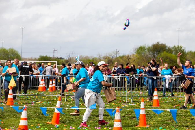 Volunteers toss large easter eggs before the arrival of a helicpoter that dropped thousands of Easter eggs at the River Fields in Northeast Philadelphia Saturday. (Brad Larrison for WHYY)