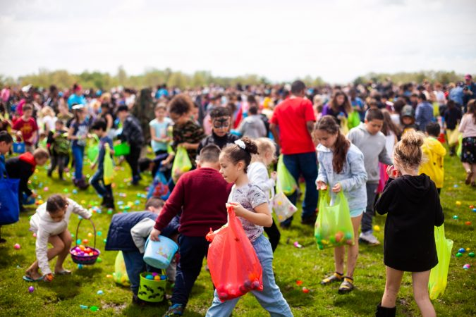 Children search for Easter eggs at the River Fields in Northeast Philadelphia Saturday after a helicopter dropped an estimated 30,000 eggs. (Brad Larrison for WHYY)