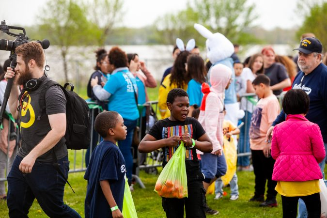 Children with their hall of Easter eggs at the River Fields in Northeast Philadelphia Saturday after a helicopter dropped an estimated 30,000 eggs. (Brad Larrison for WHYY)