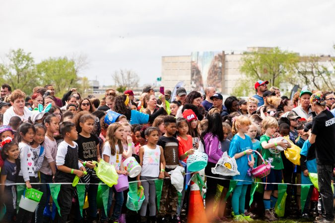 Children wait for the arrival of a helicopter that would drop thousands of Easter eggs on the River Fields in Northeast Philadelphia Saturday. (Brad Larrison for WHYY)