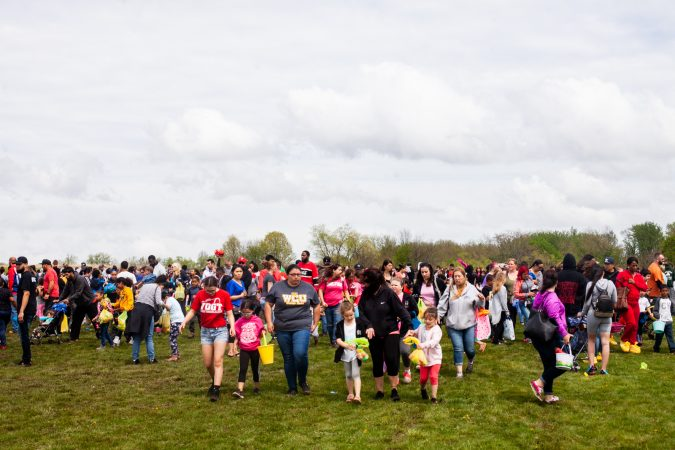 Children and parents left the River Fields in Northeast Philadelphia with their hall of Easter eggs after a helicopter dropped an estimated 30,000 eggs. (Brad Larrison for WHYY)