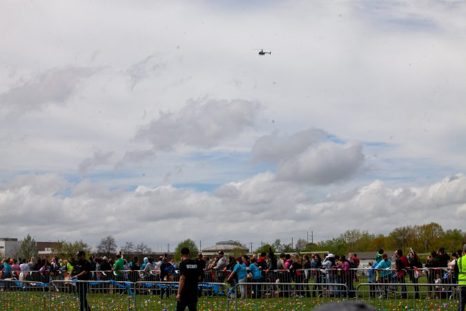 A helicopter containing a payload of an estimated 30,000 Easter eggs made its way toward the River Fields in Northeast Philadelphia Saturday. (Brad Larrison for WHYY)