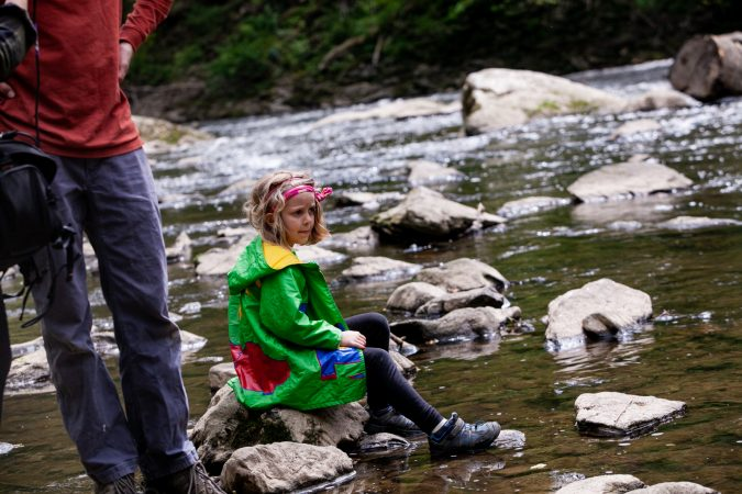 Five-year-old Ellie Sponsler sits on a rock looking for wildlife during the City Nature Challenge Sunday. (Brad Larrison for WHYY)