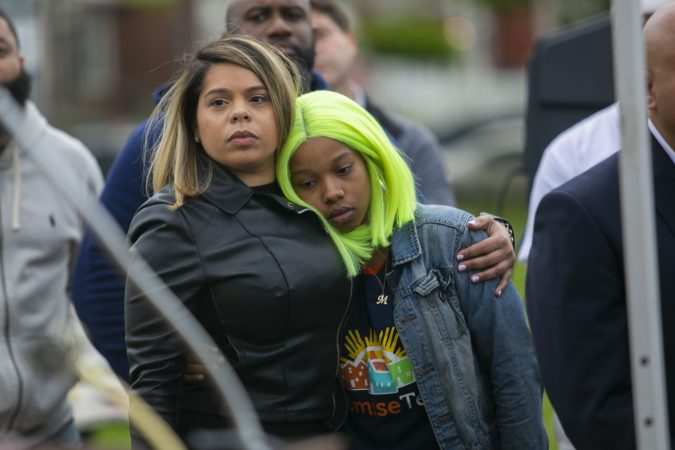 Julia Goodman lean on Janis Medina as they listen to the remark of speakers in a community rally held in Camden to create safer environment for children on Thursday, April 25, 2019. (Miguel Martinez for WHYY)