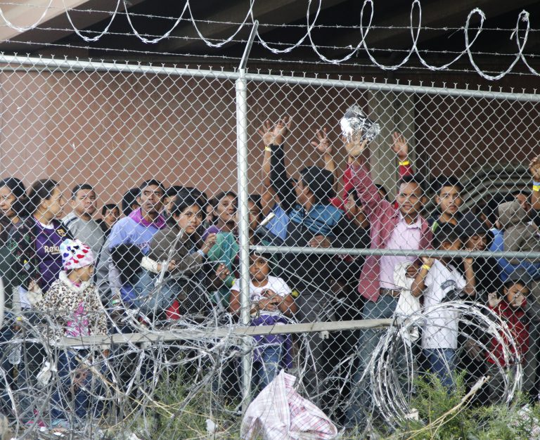 Central American migrants wait for food in El Paso, Texas, Wednesday, March 27, 2019, in a pen erected by U.S. Customs and Border Protection to process a surge of migrant families and unaccompanied minors.  (Cedar Attanasio/AP Photo)
