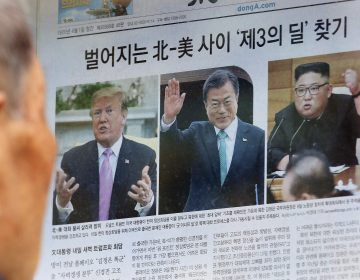A man reads a newspaper showing photos, from left of U.S. President Donald Trump, South Korean President Moon Jae-in and North Korean leader Kim Jong Un in Seoul, South Korea, last week. North Korea test-fired a