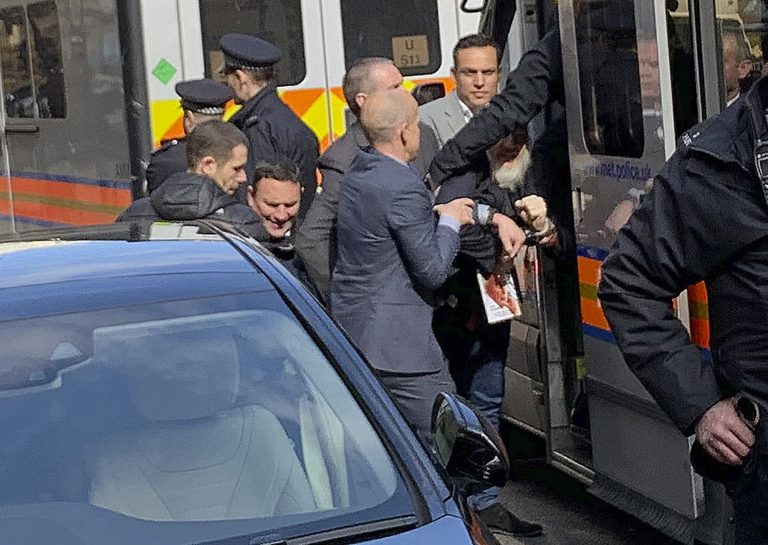 Police bundle WikiLeaks founder Julian Assange from the Ecuadorian embassy into a police van in London after he was arrested by officers from the Metropolitan Police and taken into custody Thursday April 11, 2019. (@DailyDOOH via AP)