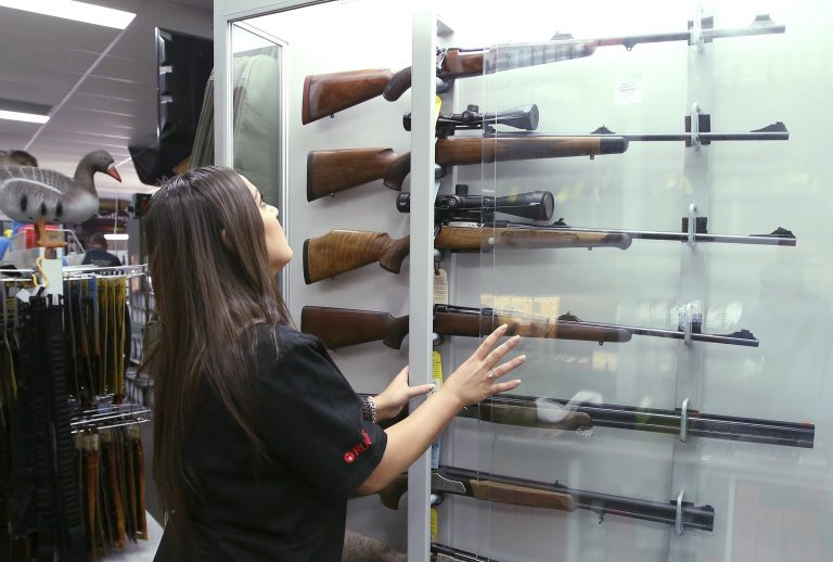 In this Wednesday, Oct. 4, 2017 file photo, a salesperson checks rifles in a gun shop display in Sydney, Australia. A documentary aired in March 2019 by Al Jazeera reported officials with Australia's far-right One Nation party met with two National Rifle Association representatives and other gun-rights advocates seeking money to undermine Australian gun laws. (Rick Rycroft/AP Photo)