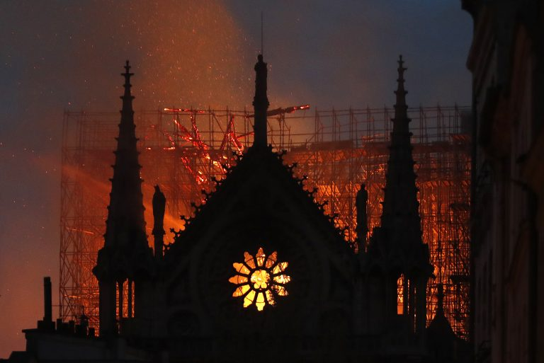 Flames and smoke rise from Notre Dame cathedral as it burns in Paris, Monday, April 15, 2019. Massive plumes of yellow brown smoke filled the air above Notre Dame Cathedral and ash fell on tourists and others around the island that marks the center of Paris. (Thibault Camus/AP Photo)