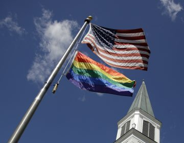 A gay pride rainbow flag flies along with the U.S. flag. (Charlie Riedel/AP Photo)