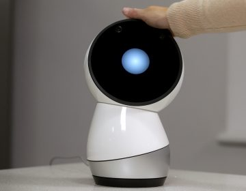 FILE - In this Nov. 21, 2017, file photo Massachusetts Institute of Technology professor and robotics researcher Cynthia Breazeal reaches to touch social robot Jibo at the company's headquarters in Boston. When robots move like humans and talk like humans, even if only a little bit, it's natural that we will treat them more like humans. (Steven Senne/AP Photo, File)