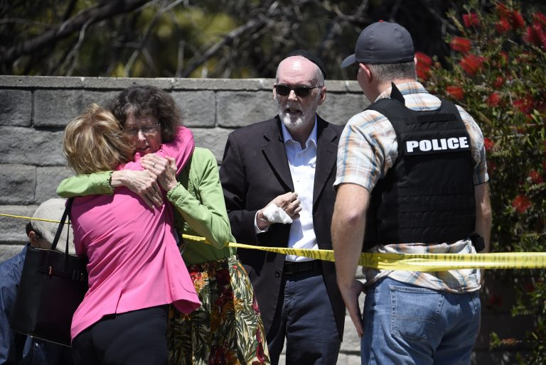 Two people hug as another talks to a San Diego County Sheriff's deputy outside of the Chabad of Poway Synagogue Saturday, April 27, 2019, in Poway, Calif. Several people have been shot and injured at a synagogue in San Diego, California, on Saturday, said San Diego County authorities. (Denis Poroy/AP Photo)
