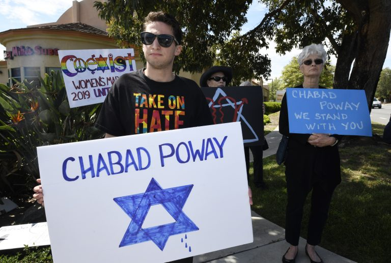 People gathering on a street corner hold signs in support of the victims of Saturday's shooting at Chabad of Poway synagogue, Sunday, April 28, 2019, in Poway, Calif. A man opened fire Saturday inside the synagogue near San Diego as worshippers celebrated the last day of a major Jewish holiday. (AP Photo/Denis Poroy)