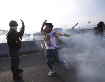 An opponent to Venezuela's President Nicolas Maduro high fives a rebel soldier on a highway overpass outside La Carlota air base amid tear gas fired by loyalist soldiers inside the base in Caracas, Venezuela, Tuesday, April 30, 2019. Venezuelan opposition leader Juan Guaidó took to the streets in Caracas with activist Leopoldo Lopez and a small contingent of heavily armed troops early Tuesday in a bold and risky call for the military to rise up and oust socialist leader Nicolas Maduro. (Boris Vergara/AP Photo)