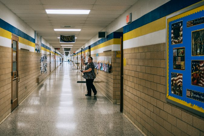 A staff member in Turkeyfoot waves hello as she gets ready for students to leave at the end of the school day. (Dani Fresh/Keystone Crossroads)
