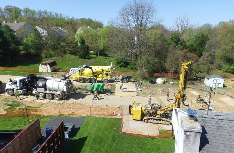 In this file photo, Mariner East 2 pipeline construction crews work in the backyards of homes on Lisa Drive in West Whiteland Township, Chester County, on May 2, 2018 after sinkholes opened in the area. That caused one of the ME2 project's many delays. (Marie Cusick/WITF)