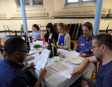 People attending the LGBTQ Seder read from the Haggadah modified by host Galia Godel to celebrate the queer Jewish experience. (Ximena Conde/WHYY)