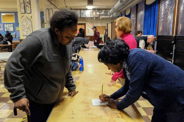 Dee McDowell (left), who is experiencing homelessness, collects her mail from volunteer Chris Martin at Broad Street Ministry on Avenue of the Arts. (Anthony Pezzoti/The Philadelphia Inquirer)