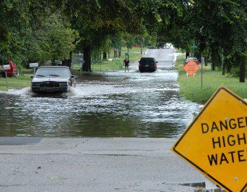 Car driving through a flooded street. (FEMA)