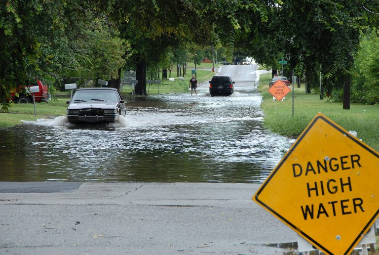 Car driving through a flooded street. (FEMA)