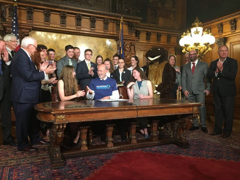 Surrounded by student supporters of the hellbender — and a mascot — Gov. Tom Wolf signs a bill officially designating the salamander as state amphibian. (Katie Meyer/WITF)