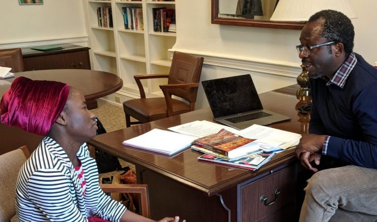 Patience Bulus speaks with Professor Jacob Udo-Udo Jacob in his office at Dickinson College. (Rachel McDevitt/WITF)