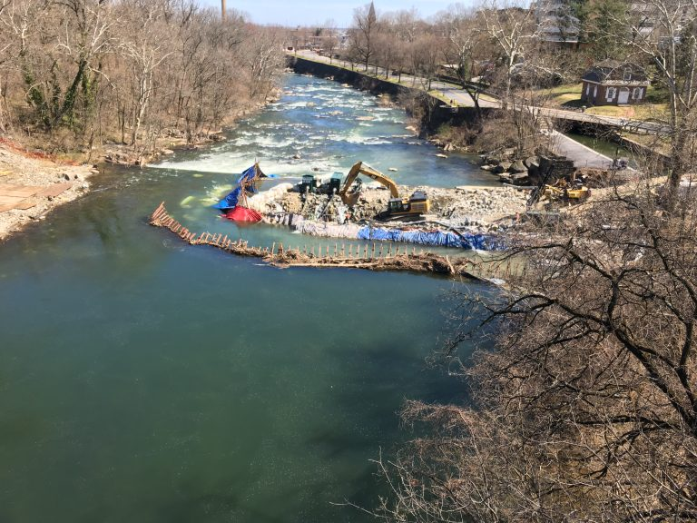 Crews in the middle of the Brandywine River work to remove a 115-year-old dam that was built to allow Wilmington water pipes to cross the river. (Mark Eichmann/WHYY)