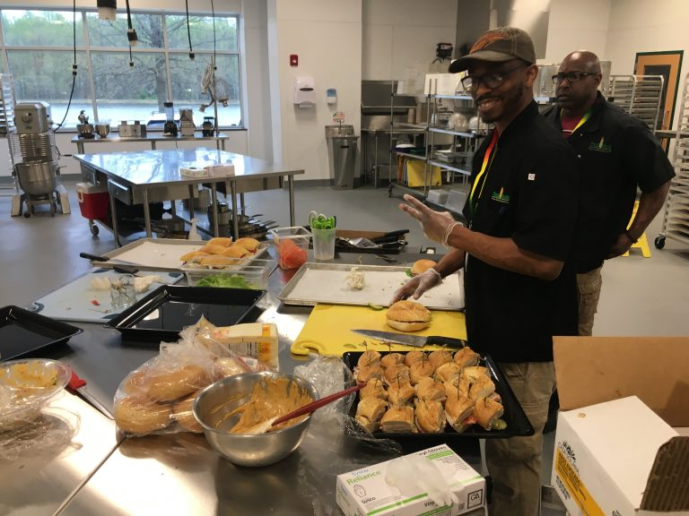 Food Bank workers prepare lunch inside the industrial kitchen at the new facility in Glasgow. The kitchen will be used for training in the expanded culinary program. (Mark Eichmann/WHYY)