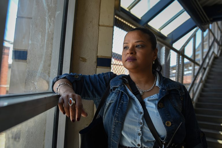 Roz Pichardo looks out the window at Kensington Avenue from inside the Somerset El station on April 27, 2019. Pichardo is a Kensington resident who works in the harm reduction community in the neighborhood. (Erin Blewett/Kensington Voice)