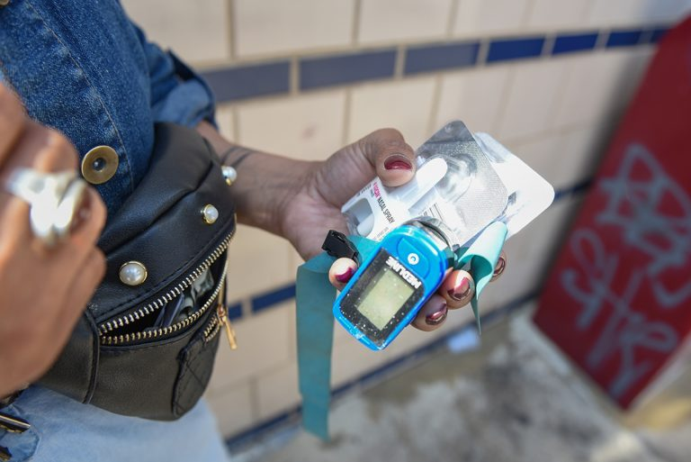 Kensington resident Roz Pichardo takes the contents out of her bag on April 27, 2019. Every day, Pichardo carries around harm reduction and emergency response supplies, like Narcan, a tourniquet, and a pulse oximeter. (Erin Blewett/Kensington Voice)