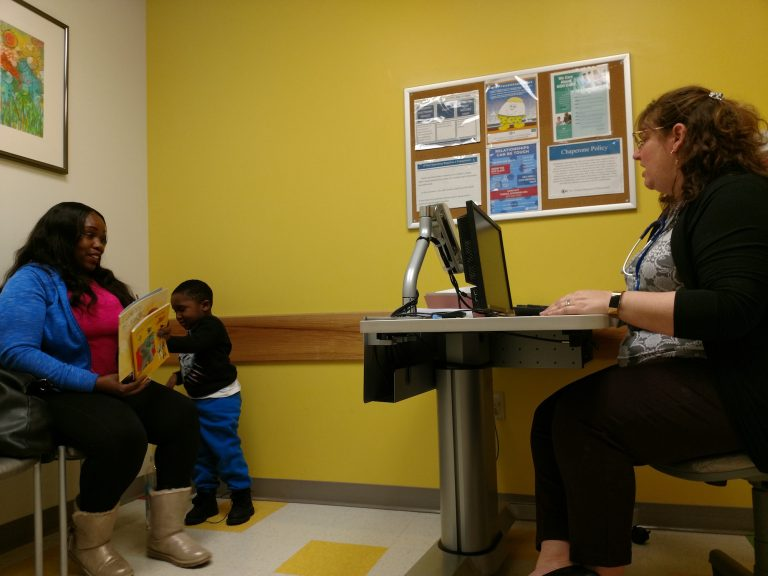 Pediatrician Eileen Everly and mom Teneika Thomas discuss Kyiren Smith's literacy progress during the 4-year-old's visit. Thomas said the boy corrected his teacher when she skipped two pages of a book she was reading in class. (Christine Bahls for WHYY)