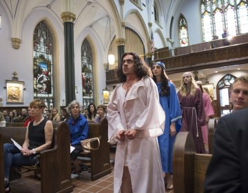 "In the opening procession of ""Via Crucis"", Jesus, portrayed by Marc Newsome, Mary, portrayed by Melanie Ashe, an the Weeping Women played by Miranda Pilate and Megan Short walk down the center aisle of St. John the Evangelist Church.   (Jonathan Wilson for WHYY)"
