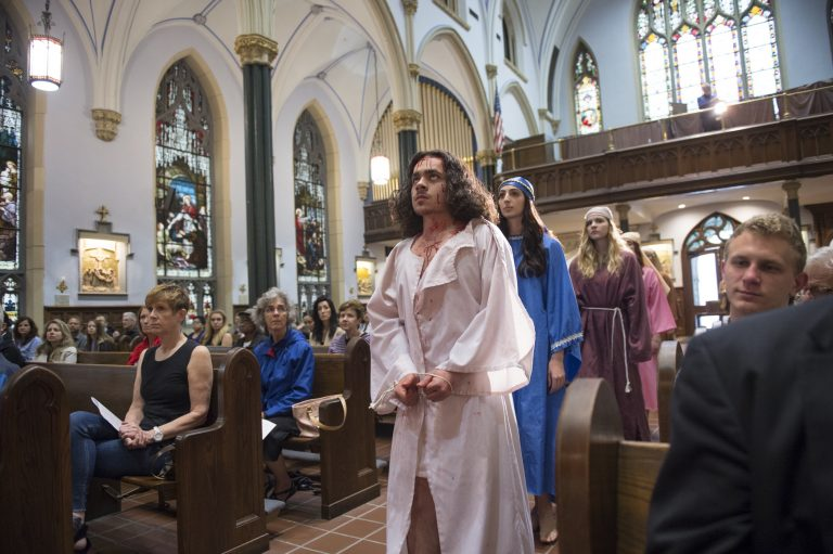 """In the opening procession of """"Via Crucis"""", Jesus, portrayed by Marc Newsome, Mary, portrayed by Melanie Ashe, an the Weeping Women played by Miranda Pilate and Megan Short walk down the center aisle of St. John the Evangelist Church.   (Jonathan Wilson for WHYY)"""