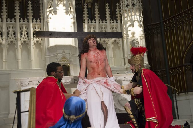 Centurions, played by Mark Samani and Radick Hastings, strip Jesus of his garments at the 10th Station of the Cross. (Jonathan Wilson for WHYY)
